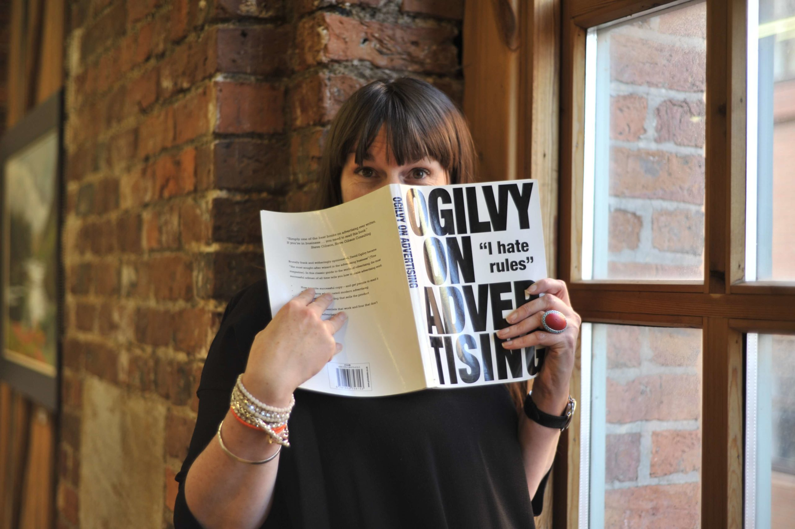 Copywriter Katherine Wildman holding her trusty copy of Ogilvy on Advertising